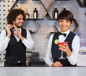 bartenders smiling and mixing drinks